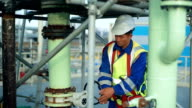 Asian worker rotating wheel at large oil refinery. video