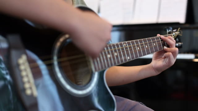 Asian young boy learning to play a Guitar video