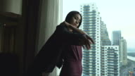 Asian young businesswoman putting on her suit. video