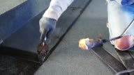 asphalt roof coating with fire, bitumen water protection layer video
