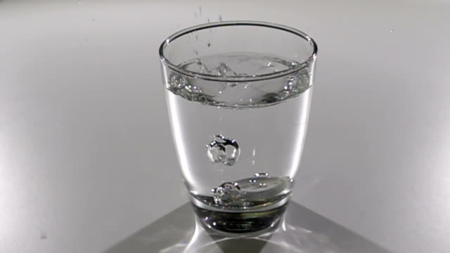 Aspirin or effervescent pill dropping into a glass of water slow motion video