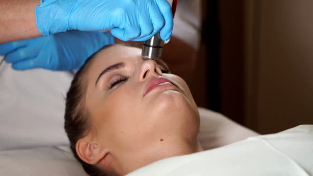 Assistant preparing woman's face for a non-injection mesotherapy treatment. video