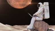 Astronaut Sitting On A Rock And Working With Computer video