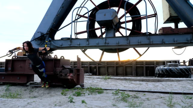 At dawn, near the cargo crane, two young beautiful, athletic girls doing exercise with trx suspension straps .Fitness exercises to work out the muscles of the whole body video
