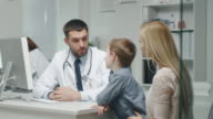 At Doctor's Office. Well Natured Male Doctor Talks and Jokes with Little Boy and His Mother. In Slow Motion. video