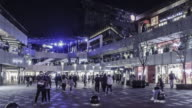 At night,walking among the fashion young people at the Sanlitun Village shopping square, Beijing, China video