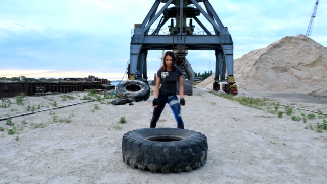 At sunrise, A young athletic woman performs exercises using a large heavy tractor wheel, coaches her muscles. Throws it. On the background can be seen cargo cranes, cargo port, dawn video