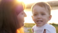 At the evening time before the sunset, baby feeling happy and smiles with her mother in the garden video