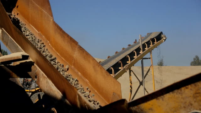 At the factory the yellow conveyor moves down coarse gravel video