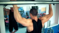 athlete doing pull-up on horizontal bar in the gym video