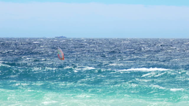 Athlete enjoying windsurfing on a summer day, extreme sport, super slow motion video