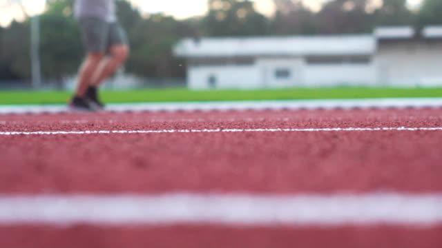 Athlete runner feet running on running track. Sport background video