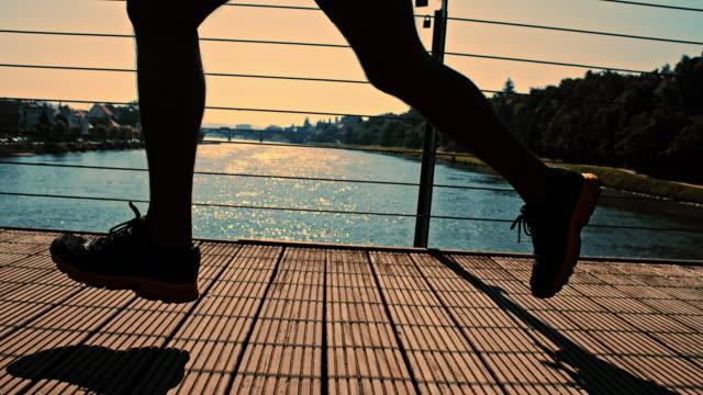 SLO MO Athlete running across the bridge at dusk video
