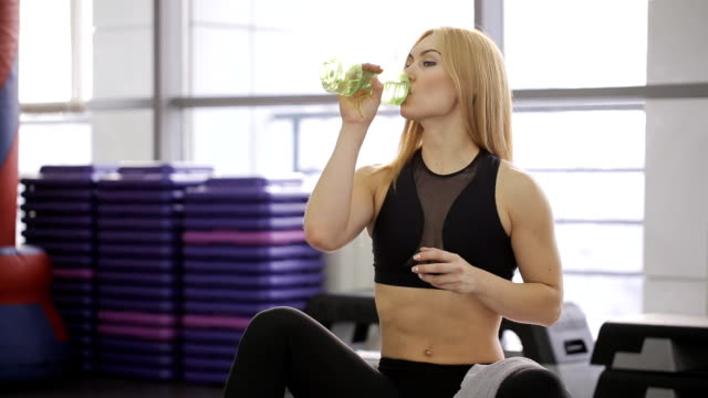 athlete sexy woman drinks water with a towel and rub the face and neck, with long hair in the gym video