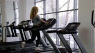 athlete sexy woman walking, with long hair walking on a treadmill in the gym in front of panoramic windows video