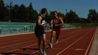 Athletes pass the baton in a track relay video