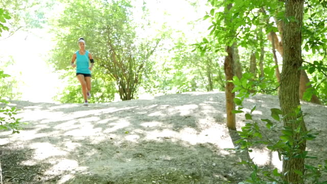 Athletic African American woman jogging up hill during off hill run at park video