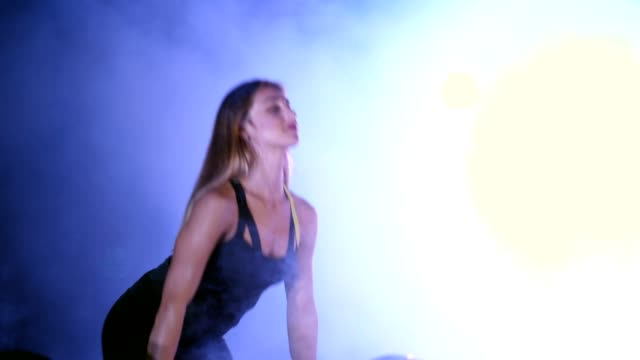 athletic, beautiful, sexy woman does exercise with the barbell, raises it. At night, in the light of multicolored searchlights, in light smoke, fog, in an old abandoned building. video