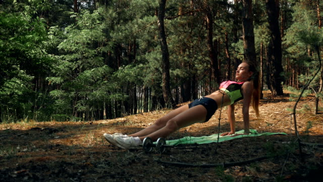 Athletic fitness girl in bright plumage stands in a lath on hands video