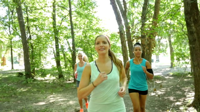 Athletic fitness isntructor leading club of off road runners in park video