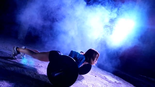athletic girl is doing push ups with a barbell, At night, in light smoke, fog, in light of multicolored searchlights, in an old abandoned hangar, building video