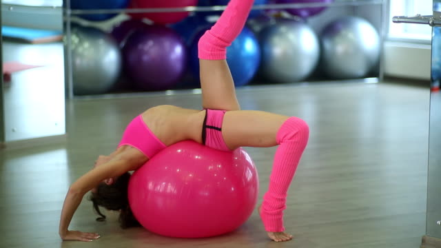 athletic girl lying on fitness ball and doing exercises for legs video