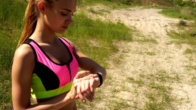 athletic girl with smart watch practicing outdoors video