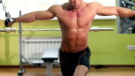 Athletic, handsome man works out on equipment in gym video