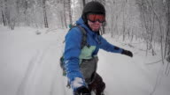 Athletic man with enjoyment rides on a snowboard on a new track in the snowy forest. It's cold, so he has dressed warm clothes video