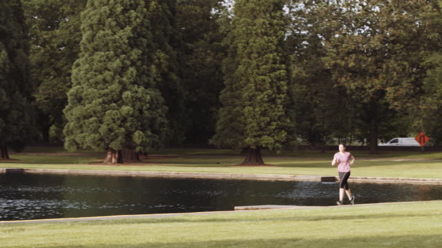 Athletic woman running along pond video