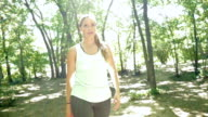 Athletic woman stretching muscles and running off road in park video