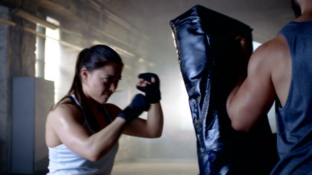 Athletic Woman Trains Her Punches on a Punching Bag that Her Partner/ Trainer Holds. She's Strong and Gorgeous Woman. They Workout in a Gym. video