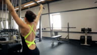 Athletic woman uses a lat pull-down machine sitting back to the camera video