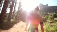 Athletic woman walking away on a mountain nature trail with sunflare video