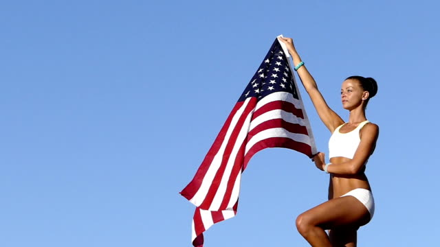 Athletic Woman with american flag slow motion video