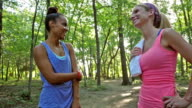 Athletic women talking before running outdoors in sunny park video