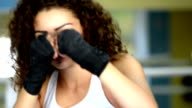 Athletic young curly woman shadow boxing, front view, slow motion video
