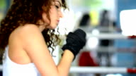 Athletic young curly woman shadow boxing, side view, slow motion video