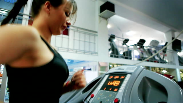 athletic young girl goes in for sports, young woman running, cardio training, treadmill, girl is engaged on a simulator in the gym, sport for slender figure video