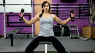 Athletic young woman deals with dumbbells in the gym video