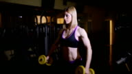 athletic young woman doing exercises with dumbbells in the gym, video