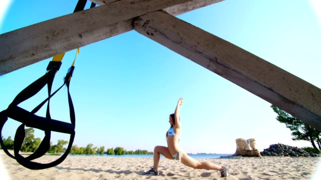 athletic, young woman in swimsuit doing stretching, balance exercises. close-up, hanging fitness trx system, TRX suspension straps. On the beach, in summer, in sun rays video