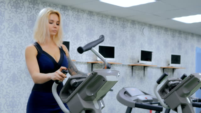 Athletic young woman working out on stepper machine at the gym video