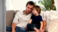 Attentive father watching tv with his son video