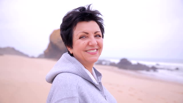 Attractive active mature woman standing on an ocean beach and smiling at camera. video