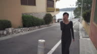 Attractive adult woman walking on the sidewalk talking on the smartphone video