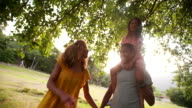 Attractive African-American family having a stroll together in beautiful park video