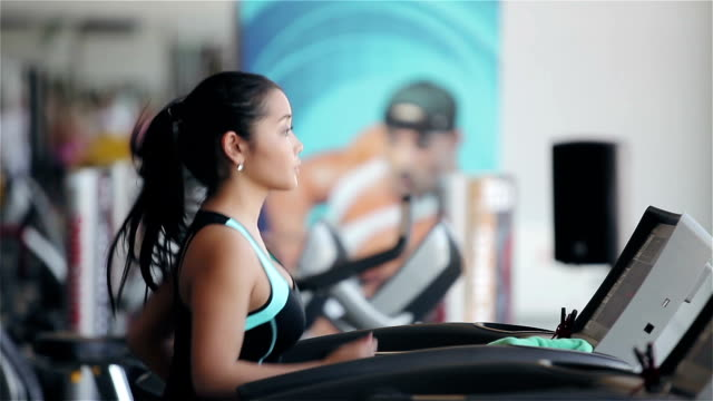 Attractive asian girl running on the treadmill in the gym video