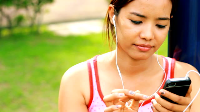 Attractive Asian with Music Player Close up video