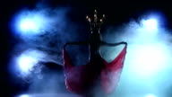 Attractive belly dancer continue dancing with candles on her head, black, smoke, silhouette video